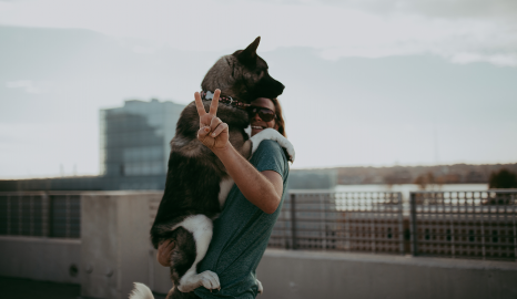 Vibrant member on rooftop holding dog doing peace sign
